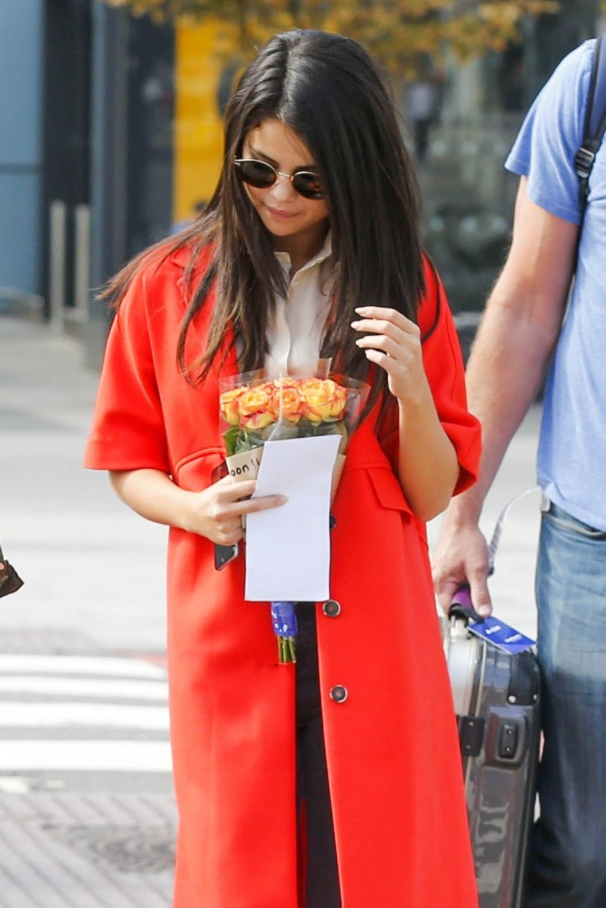 Picture Shows: Selena Gomez September 20, 2015 Selena Gomez seen arriving at Heathrow Airport in London, UK. Selena was dressed stylishly in a long red coat, a cream blouse, ripped grey jeans and leopard print pumps as she carried a bouquet of roses given to her by some fans. Non-Exclusive WORLDWIDE RIGHTS Pictures by : FameFlynet UK © 2015 Tel : +44 (0)20 3551 5049 Email : info@fameflynet.uk.com